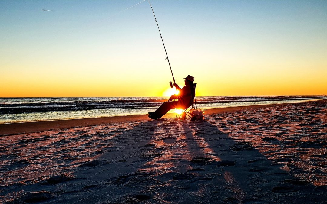 active senior fishing in the ocean at golden hour right after happy hour shadows sand shore florida